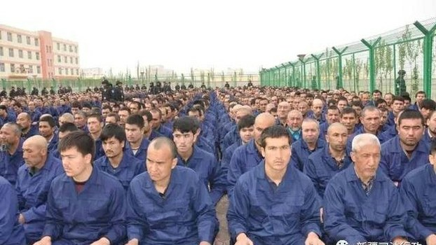 A photo posted to the WeChat account of the Xinjiang Judicial Administration shows Uyghur detainees listening to a 'de-radicalization' speech at a re-education camp in Hotan prefecture's Lop county, April 2017.