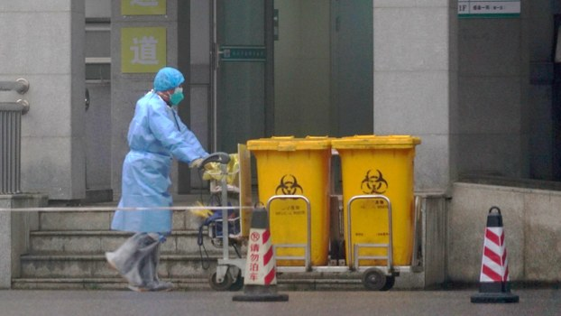 Staff move bio-waste containers past the entrance of the Wuhan Medical Treatment Center, where some infected with a new virus are being treated, in Wuhan, China, Jan. 22, 2020.