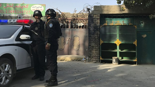 Police officers are shown on duty outside a suspected internment center in Xinjiang's Korla city, Nov. 2, 2017.