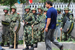 A Uyghur man walks past armed Chinese security forces in Urumqi, July 17, 2009.