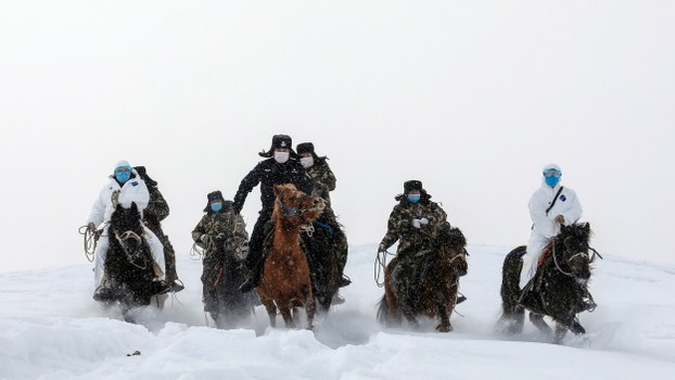 Police officers wearing protective face masks ride horses on their way to visit residents who live in remote areas of Xinjiang's Altay region, to promote the awareness of the coronavirus, Feb. 19, 2020.
