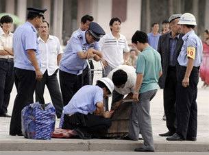 Ethnic Uyghurs' bags are searched in the main square in Xinjiang's famed Silk Road city of Kashgar on August 8, 2008.