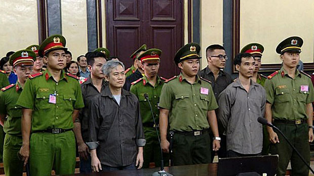 Activist Luu Van Vinh (L) and other members of the Vietnam National Self-Determination Coalition appear in court in Ho Chi Minh City on Oct. 5, 2018.