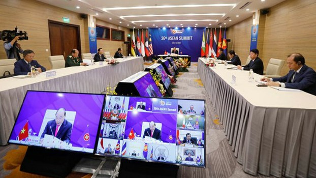 Vietnamese Prime Minister Nguyen Xuan Phuc (center and on screen) addresses regional leaders during the virtual ASEAN Summit from Hanoi, June 26, 2020.