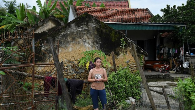 A Vietnamese woman stands outside her house in Yen Thanh district of Vietnam's Nghe An province, the chief source of  migrants among 39 people found dead in a truck in Britain, Oct. 27, 2019.