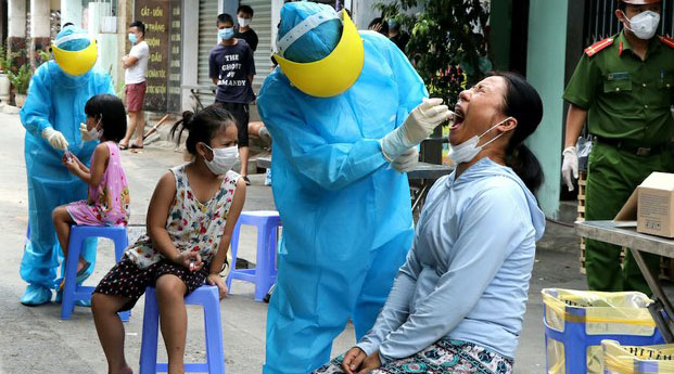 Medical workers test city residents in Vietnam's Danang for COVID-19 infection, Aug. 3, 2020.
