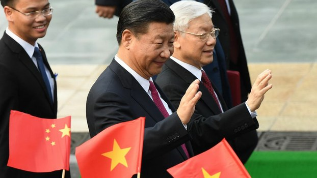 Chinese President Xi Jinping (C) and Vietnam's Communist Party Secretary General Nguyen Phu Trong (R) wave during a welcoming ceremony at the presidential palace in Hanoi, Nov. 12, 2017.