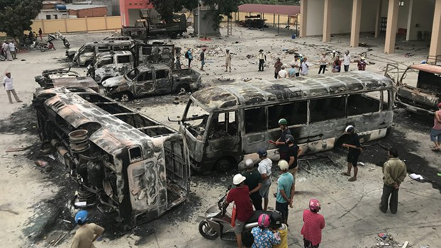 Charred buses sit at a police station compound in Binh Thuan province following clashes over a government proposal on special economic zones, June 12, 2018.