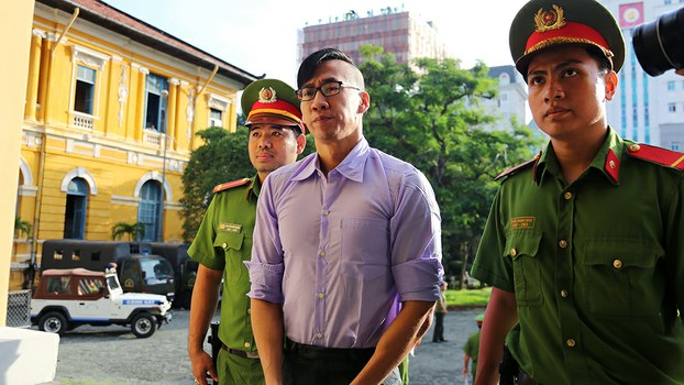 Will Nguyen (C) is escorted by policemen to a courtroom for his trial in Ho Chi Minh City, July 20, 2018.