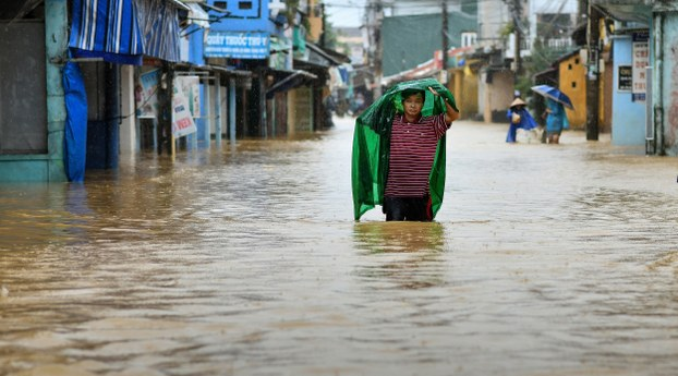 A man walks through flood waters in central Vietnam's city of Hue, Oct. 17, 2020.