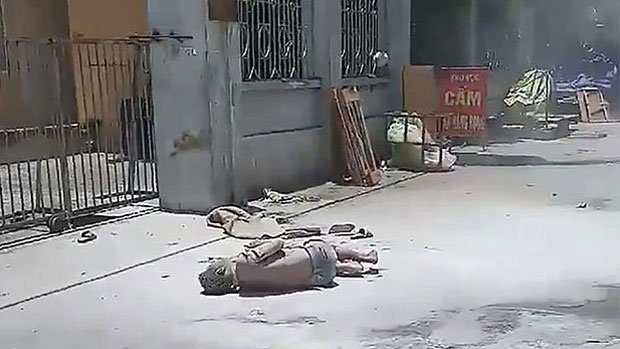 Vietnamese petitioner Bui Huu Tuan lies badly burned after setting himself on fire outside a government office in Hanoi, July 2, 2018.