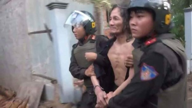Vuong Van Tha is taken into custody by police officers in An Giang province's An Phu district, May 18, 2017.