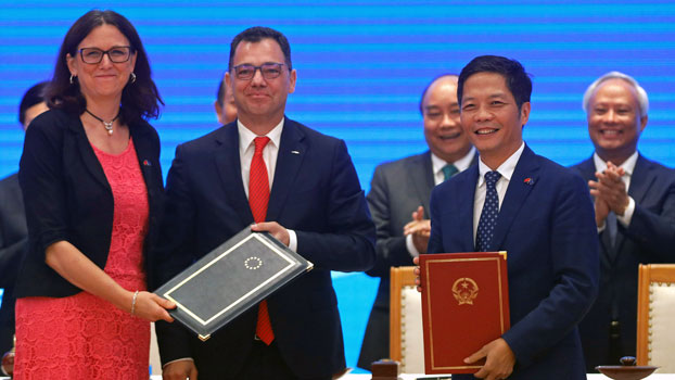 European Trade Commissioner Cecilia Malmström (L), Romania's Minister for Business Environment, Trade and Entrepreneurship Ștefan-Radu Oprea (C), and Vietnam's Industry and Trade Minister Tran Tuan Anh (2nd from R) exchange documents during the signing ceremony of the EU-Vietnam Free Trade Agreement in Vietnam's capital Hanoi, June 30, 2019.