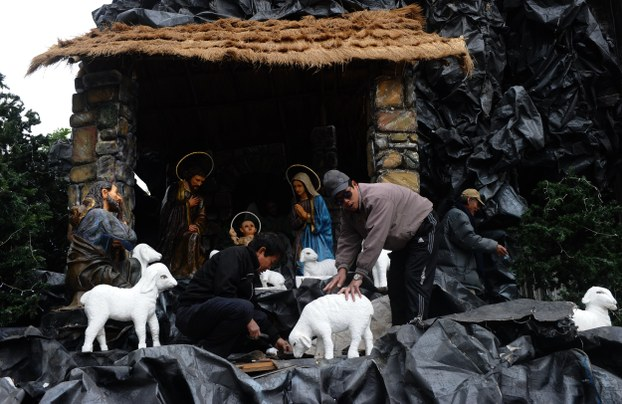 Workers install a model depicting the Christ's nativity scene on the door steps of Hanoi's Cathedral on December 16, 2014.