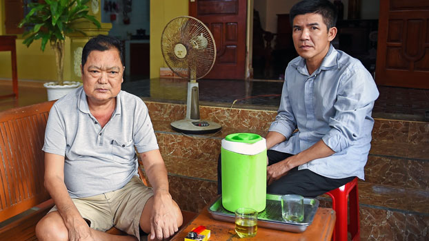 Nguyen Le (L), father of 33-year-old Nguyen Van Hung who is feared to be among the 39 people found dead in a truck in Britain, sits outside his house in Dien Chau district of Vietnam's Nghe An province, Oct. 28, 2019.