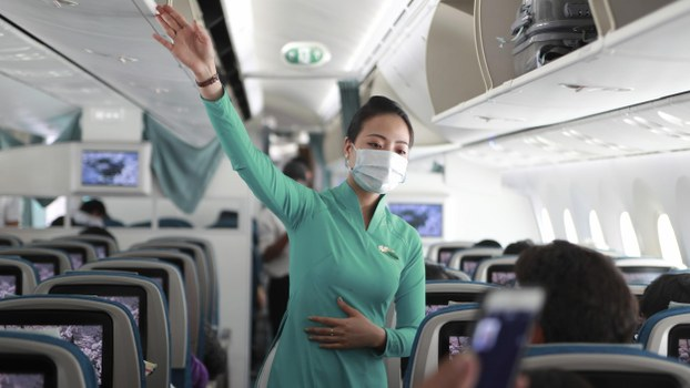 A flight attendant gives instructions to passengers on a plane in Ho Chi Minh City, Vietnam on Monday, March 16, 2020.