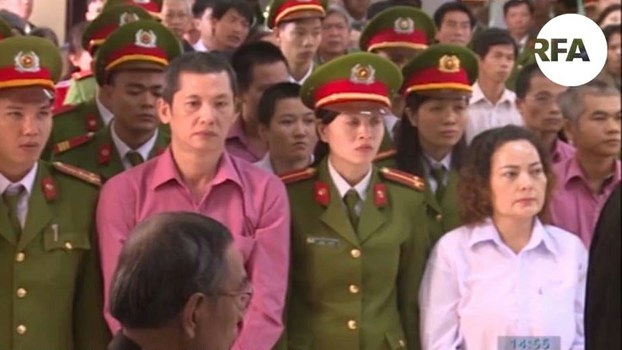A screenshot from closed circuit television shows the nine defendants at trial in the People's Court of Binh Dinh Province, Dec. 28, 2017.