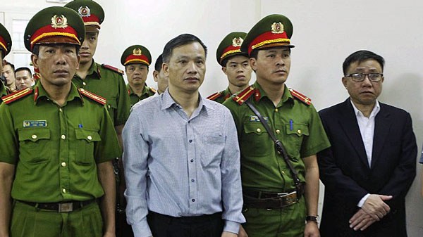 Prominent Vietnamese rights lawyer Nguyen Van Dai (C) stands in a courtroom during his trial with other political activists in Hanoi, April 5, 2018.