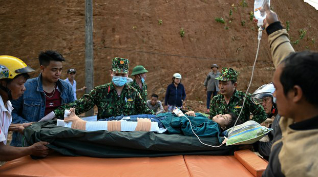 Vietnamese soldiers rescue a resident from a landslide in Quang Nam province's Tra My district, Oct. 29, 2020.