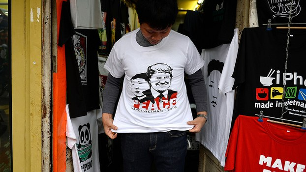 A Vietnamese customer tries on a T-shirt with portraits of US President Donald Trump and North Korean leader Kim Jong Un at a shop in Hanoi, Feb. 22, 2019.