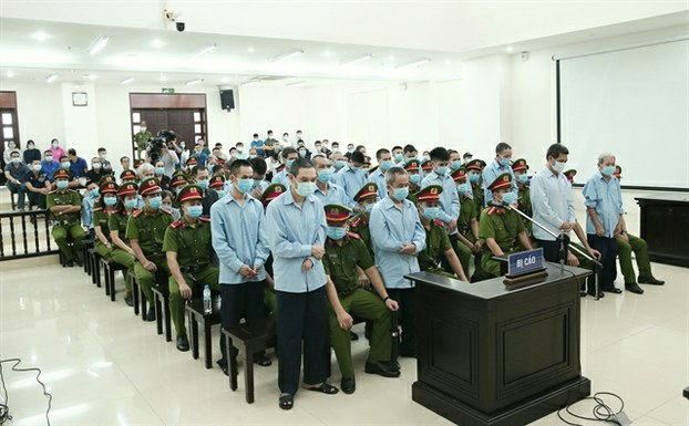Defendants in Vietnam's Dong Tam trial stand to hear their sentences in a court in Hanoi, Sept. 14, 2020.