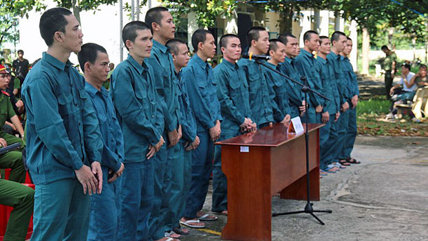 Vietnamese defendants charged with disrupting public order by participating in a violent protest in June against a proposed law on special economic zones stand during an outdoor trial in southeastern Vietnam's Binh Thuan province, Sept. 26, 2018.