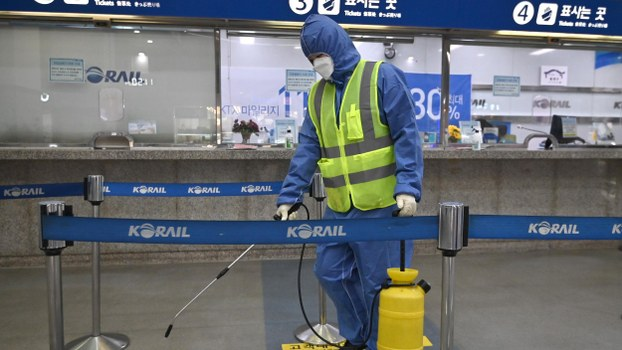 A worker wearing protective gear sprays disinfectant as part of preventive measures against the spread of the COVID-19 coronavirus, at a railway station in Daegu, South Korea on February 26, 2020.