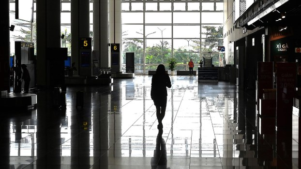 A woman walks in the nearly empty arrival hall of Noi Bai International Airport in Hanoi on February 27, 2020, as the number of air travellers has plummeted amid fears over the spread of the COVID-19 coronavirus.