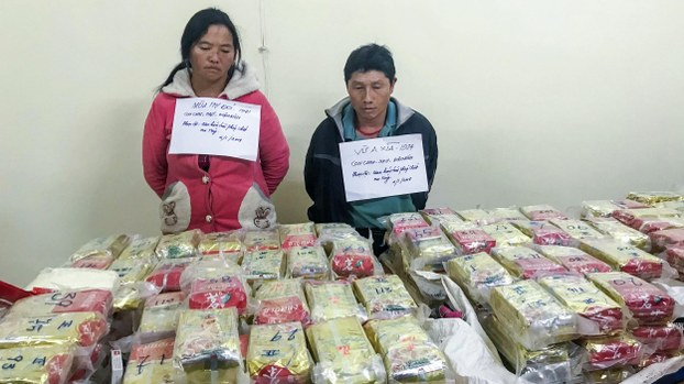 This picture taken on January 2, 2018 shows arrested ethnic H'mong couple Vu Chu Senh (R), 44, and his wife Mua Thi Do, 39, posing behind a table with 489 packs of heroin (170 kgs) they attempted to smuggle into Vietnam from Laos, at a police station in the northwestern province of Dien Bien.