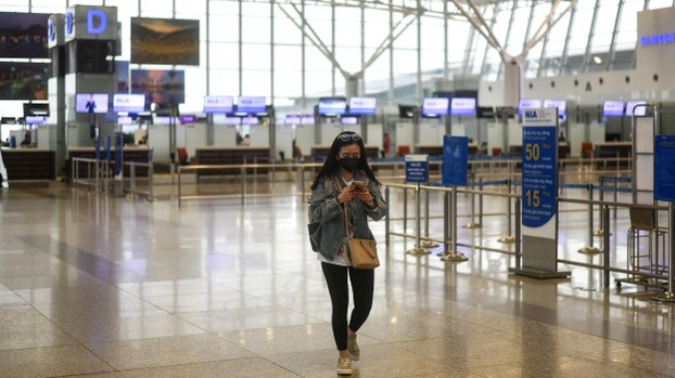 A passenger wearing a face mask walks in the nearly empty departure hall of Noi Bai International Airport in Hanoi on March 12, 2020 as numbers of air travellers in the region plummeted amid fears over the spread of the COVID-19 coronavirus.
