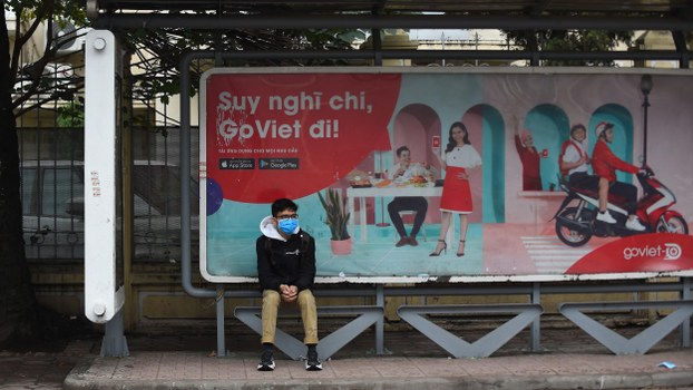 A man wearing a protective facemask sits at a bus stop in Hanoi on February 4, 2020, amid concerns of the novel coronavirus outbreak, which originated in China's Wuhan late last year.
