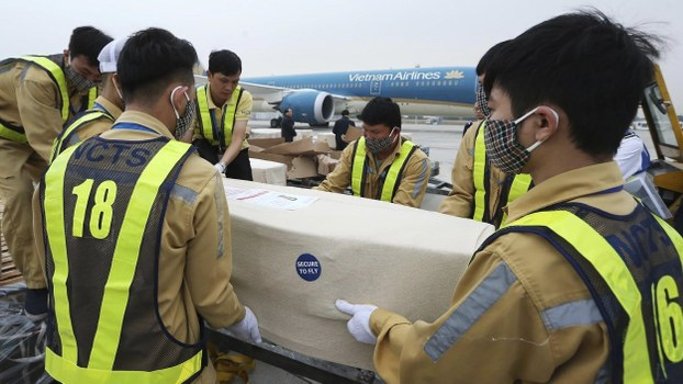 Airport personnel carry a coffin containing a body repatriated from the U.K. on the tarmac of the Noi Bai airport on Wednesday, Nov. 27, 2019 in Hanoi, Vietnam.