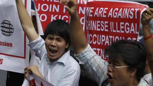 Vietnamese expatriates shout slogans as they join a rally by Filipinos in front of the Chinese Consulate at the financial district of Makati city to protest the recent moves by China to construct an oil rig near the Vietnamese-claimed Paracels off the contested Spratlys group of islands and shoals in the South China Sea Friday, May 16, 2014.