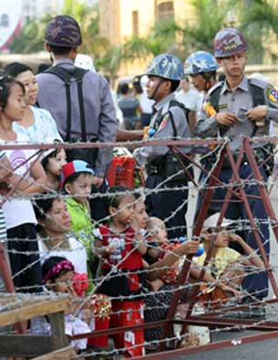 Security officials watch as people gather to celebrate a festival in Rangoon, April 13, 2008.