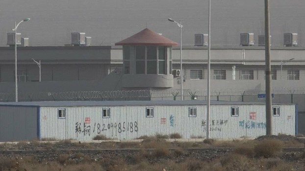A guard tower and barbed wire fences are seen around an internment camp in the XUAR's Atush city, Dec. 3, 2018.
